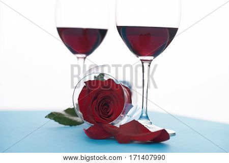 Wineglasses and rosebud on white. Love card concept Valentine's day theme