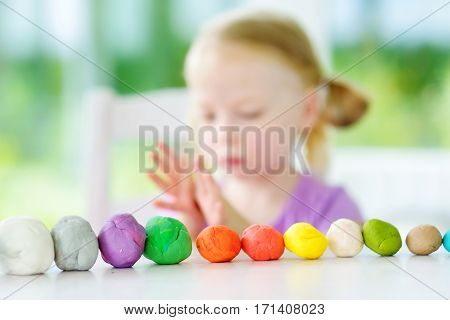 Cute Little Girl Having Fun With Modeling Clay At A Daycare. Creative Kid Molding At Home.