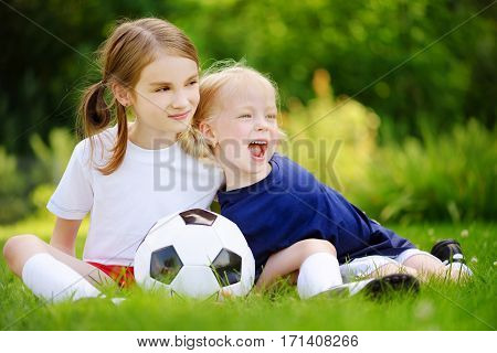 Two Cute Little Sisters Having Fun Playing A Soccer Game
