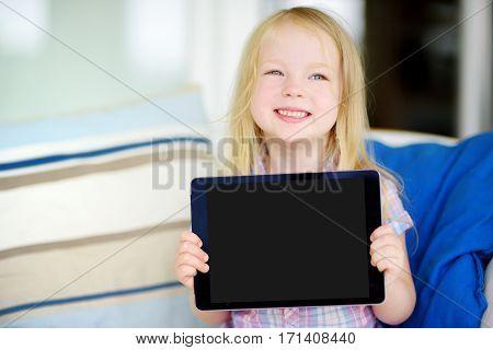 Smart Little Schoolgirl With Digital Tablet In At Home