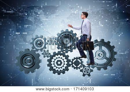 Businessman in teamwork concept with cog wheels