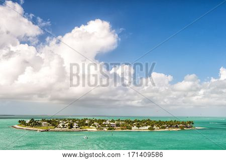 touristic boat or yacht floating by island with houses and green trees on turquoise water and blue cloudy sky yachting and isle life around beautiful Key West Florida USA