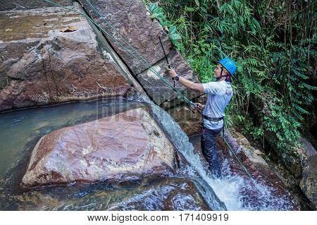 Beaufort,Sabah,Malaysia-Jan 28,2017:Adventure man rappelling Jempangah waterfall in Beaufort,Sabah,Borneo.Waterfall Abseiling activity adventure getting famous in Sabah,Borneo,Malaysia
