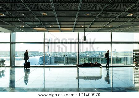 People With Luggage Waiting Hall Of Airport At Window Glass