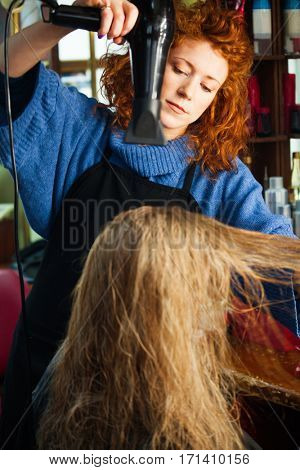 young woman in her hair studio do hair style to female customer small business concept