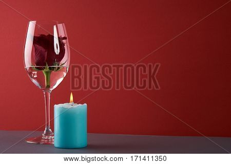 Wineglass with rosebud inside candle and heart on red background. Love card concept with copy space. Valentine's day theme