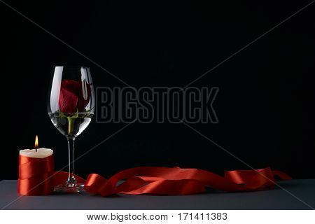 Wineglass with rosebud inside candle and red ribbon on dark background. Love card concept with copy space. Valentine's day theme