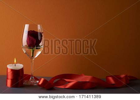 Wineglass with rosebud inside candle and red ribbon on orange background. Love card concept with copy space. Valentine's day theme