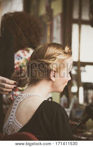 woman making braids at hair studio closeup
