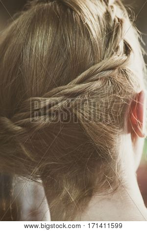 closeup of blonde woman hair with braid back view