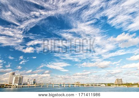Water Channel With Bridge And Houses On Cloudy Blue Sky