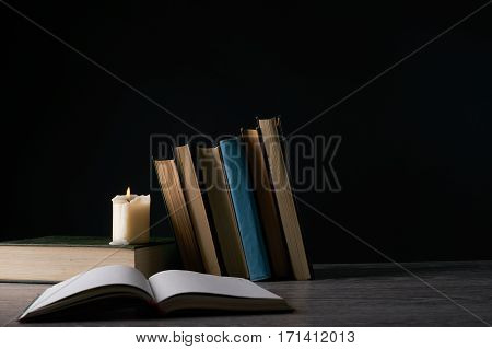 Book and candle on wooden table against dark background. Education knowledge concept with copy space