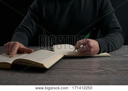left-hander man studying at wooden table .