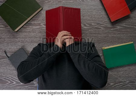Exhausted student fall asleep with a book on his face. Top view