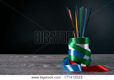 Assortment of colored pencils and handmade pencil box on wooden table.Black background with copy space.