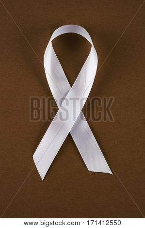 White awareness ribbon on brown background. Symbol of anti-violence against women safe motherhood