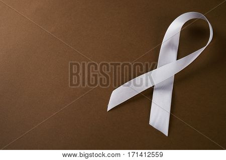 White awareness ribbon on brown background. Symbol of anti violence against women safe motherhood. Top vew with copy spaced