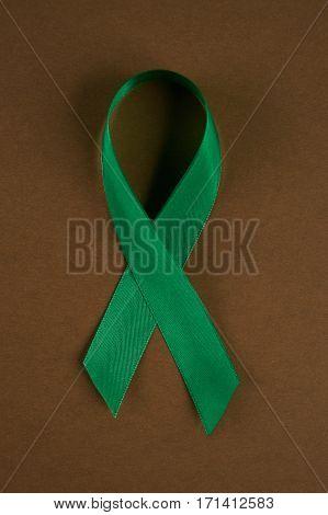 Green awareness ribbon on brown background. Symbol of Mental Health
