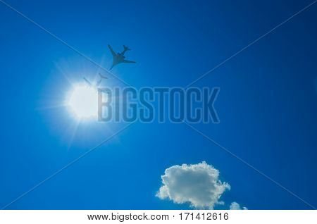 two bombers fly down through the sun against a blue sky