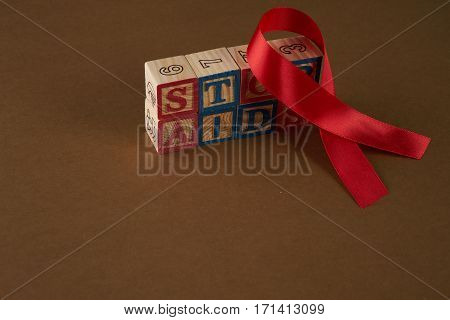 Stop AIDS on Cubes with letters and red awareness ribbon on a table
