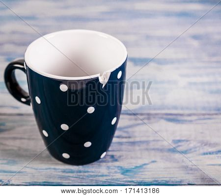 Broken black ceramic cup, on blue wooden background, free space