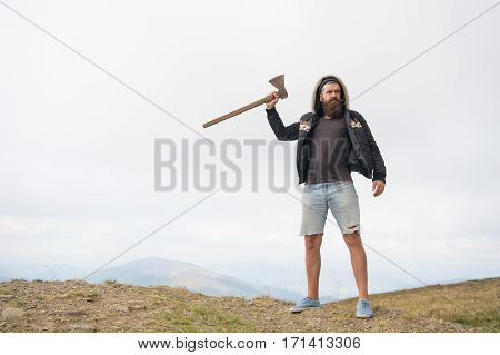 Bearded Man, Brutal Hipster With Moustache Holds Axe On Mountain