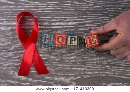 Red awareness ribbon and hope word on cubes with letters. Symbol of solidarity with people living with HIV AIDS