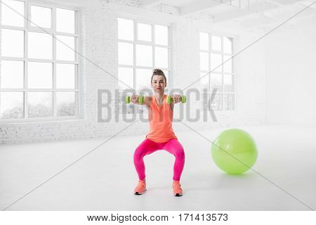 Young woman in colorful sportswear squatting with dumbbels in the white gym with fitness ball on the floor