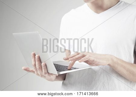 Close-up view of modern laptop in man's hands guy wearing white t-shirt working on portable computer. White background in studio