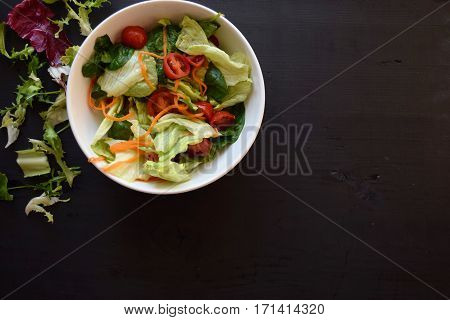 Bowl of fresh green salad, tomatoes, cucumber on wood table against dark background, with salt, olive, sunflower oil, pepper