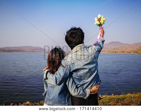 back view couples in jeans jecket standing happy cliffside looking sea view Kalasin Thailand