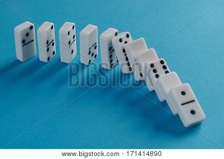 White toppling domino play pieces on blue background. Chain reaction