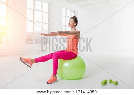Young woman in colorful sportswear doing fitness with fitness ball in the white gym