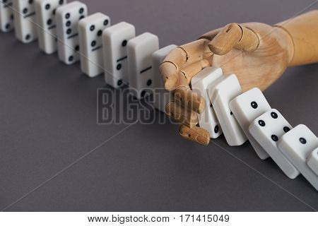 Wooden hand trying to stop toppling dominoes on table. Chain Reaction poster