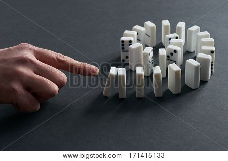 Hand Starting Dominoes Continuous Toppling. Chain Reaction Domino Effect