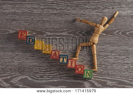 Education concept. Wooden figurine on stairs made of wooden cubes with letters