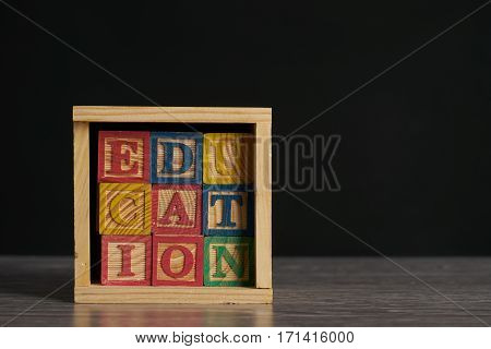 Education word on wooden cubes with letters in wooden box