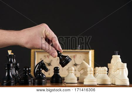 Close up of hand holding pawn chess piece playing quick chess with timer on dark background.