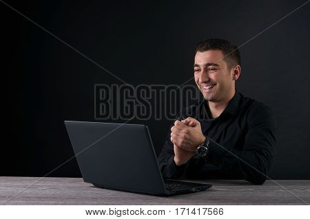 Satisfied with work done. Happy young man working on laptop. Dark background with copy space