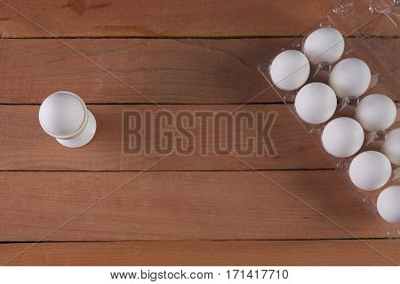Egg cup and egg tray on wooden background. Top view