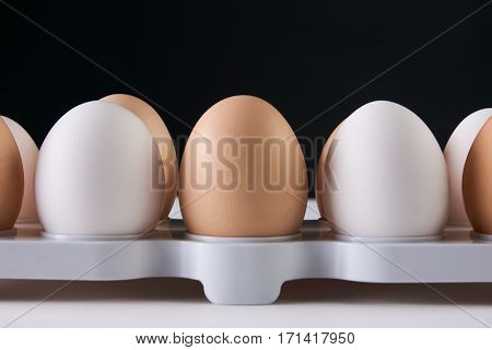 Egg tray with white and brown eggs . Close up