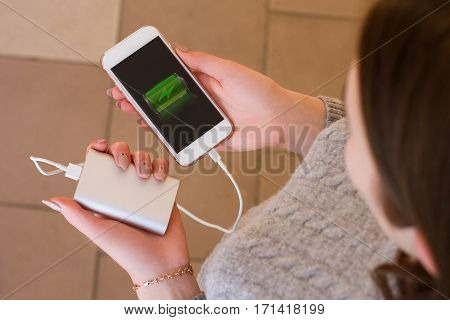 Girl Hold In Hands Smart Phone And Power Bank. Charge Smart Phon