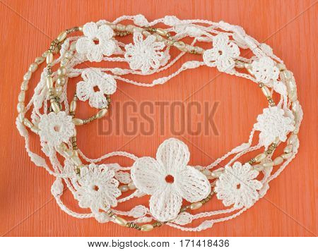 Handmade crocheted cotton organic lace wreath. White knitted frame pattern handicraft background needlework creative craft. Tender crochet wreath with flowers pearl beads place for text