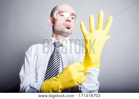 Man in white shirt in yellow latex gloves and plastic glasses