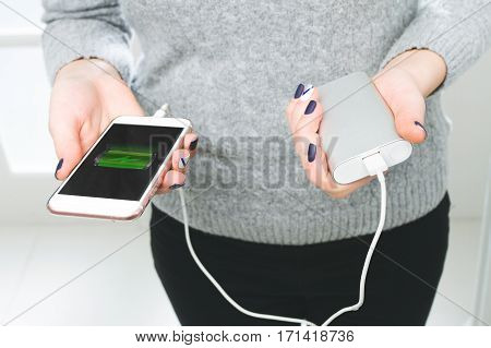 Two Girls Hands Hold Of The Phone And Charger. Powerbank And Sma
