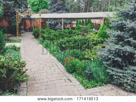 Beautiful landscape design, garden path to gazebo, evergreen bushes and shrubs in sunlight. Modern landscaping. Summer garden or park design.