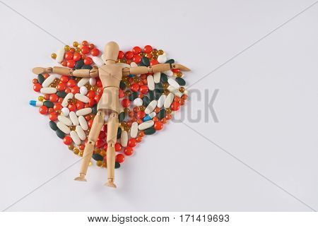 Wooden figurine on different pills laid out in the form of heart on a white background