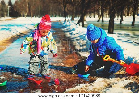 little boy and girl plaing with paper boats in spring water puddle