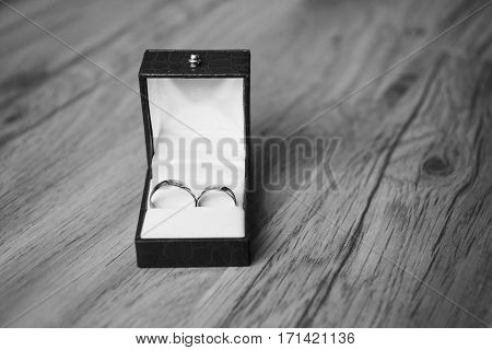 Black and white art photography monochrome wedding rings on red box wedding bands on wooden background