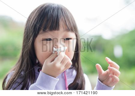 little girl get cold and blow her nose asian